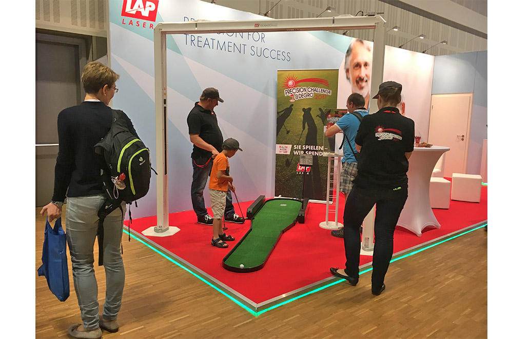 LAP booth at DEGRO 2017 a young kid playing mini golf for charity